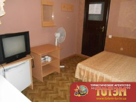Комната с кроватью, холодильником, зеркалом, телевизором, вешалкой, двумя тумбочками, вентилятором и посудой со столовыми приборами в 2, 3-х местном номере полулюкс в Атлантисе