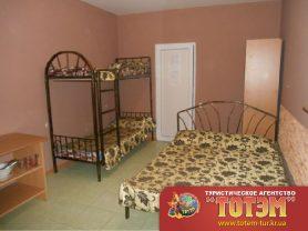 Комната с двухспальной и двухьярусной кроватями с тумбочкой и шкафчиком
