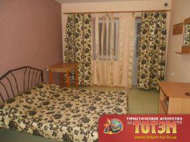 Комната с кроватью, столиком, тумбочкой и выходом на общий балкон в 5, 6-ти местном номере в Атлантисе
