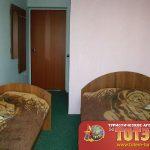 Комната с двумя кроватями и зеркалом в санатории Фрегат