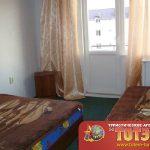 Комната с двумя кроватями и тумбочками и выходом на балкон в санатории Фрегат