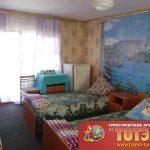 Комната с двумя кроватями с холодильником, тумбочкой, стулом и орнаментом в 2-4х местном номере базы отдыха Александрия