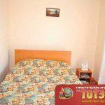 Комната с двухспальной кроватью, тумбочкой и картиной в пансионате Амазонка