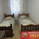 Комната с двумя кроватями и стулом в 2-4х местном номере в пансионате Гелистин